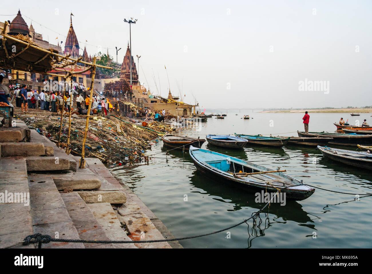 Varanasi, Uttar Pradesh, India : un uomo in piedi su una barca sul fiume Gange guarda le cremazioni al Manikarnika Ghat. Secondo l induismo una dea Immagini Stock