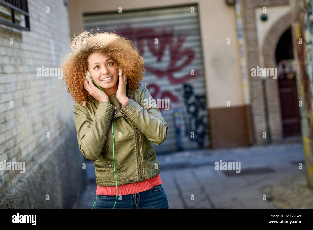 0a48ce3d16 Ritratto di giovane attraente ragazza nera in background urbano ascoltando  la musica con le cuffie.