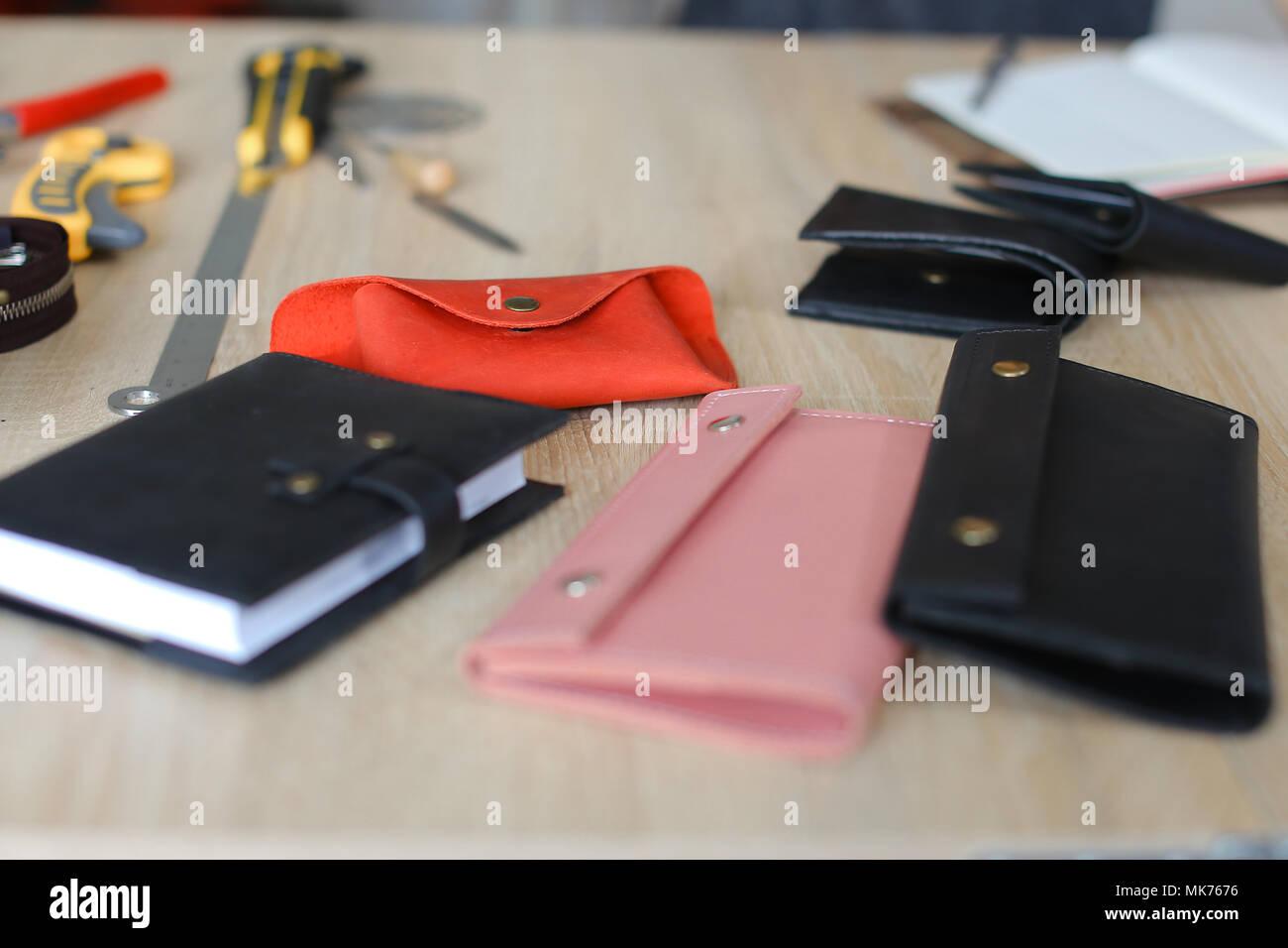 2764838093 Fatte a mano portafogli in pelle e il notebook sul tavolo in atelier.  Immagini Stock