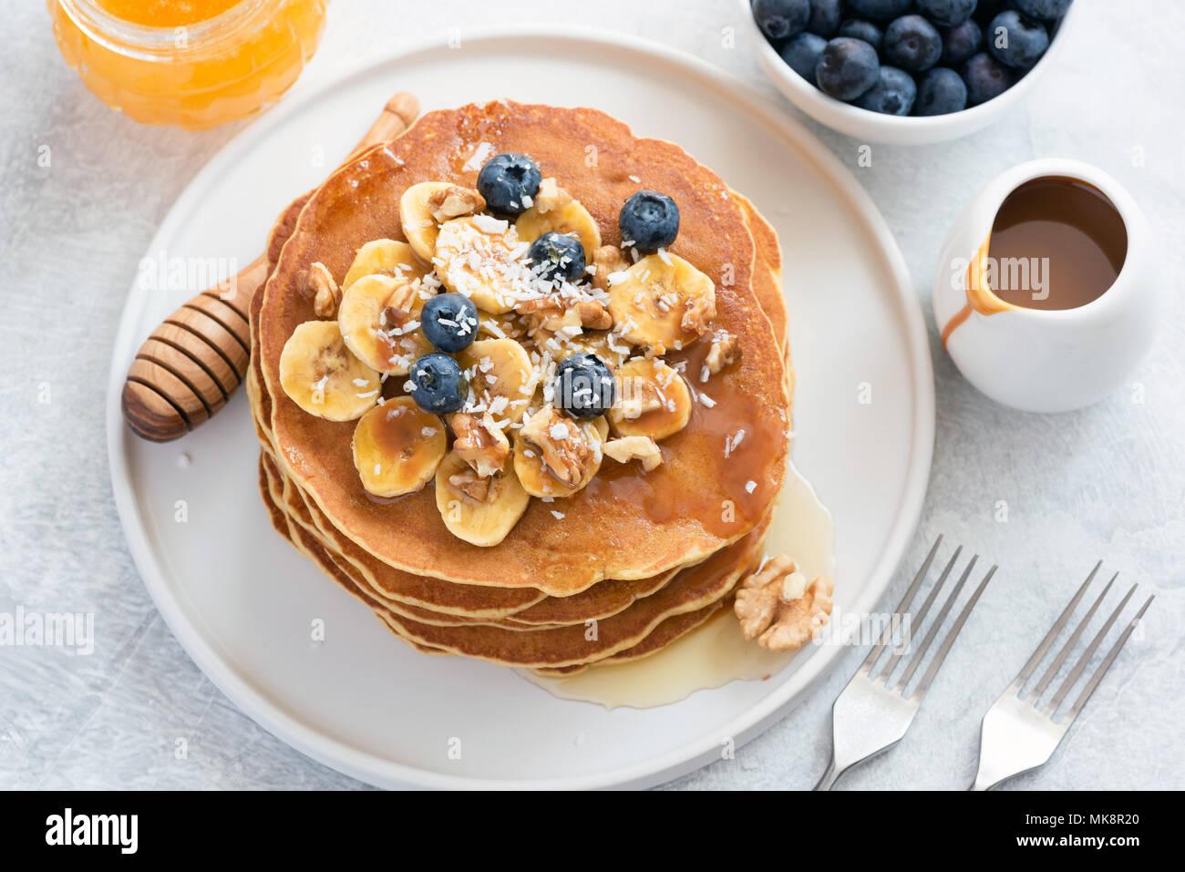 Pancake con mirtilli, banana, noci e miele sulla piastra bianca. Pila di gustosi pancake con sciroppo di caramello. Frittelle prima colazione con miele Immagini Stock
