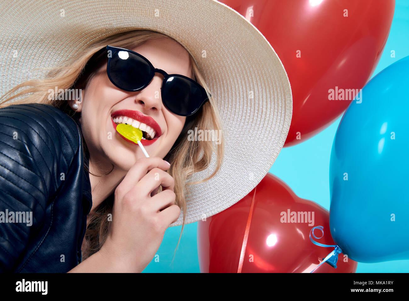 Bella ragazza a bilanciere in giacca di pelle e occhiali da sole con cuore lolipop sagomato a forma di cuore palloncini. Raffreddare attraente giovane donna moda portra Foto Stock