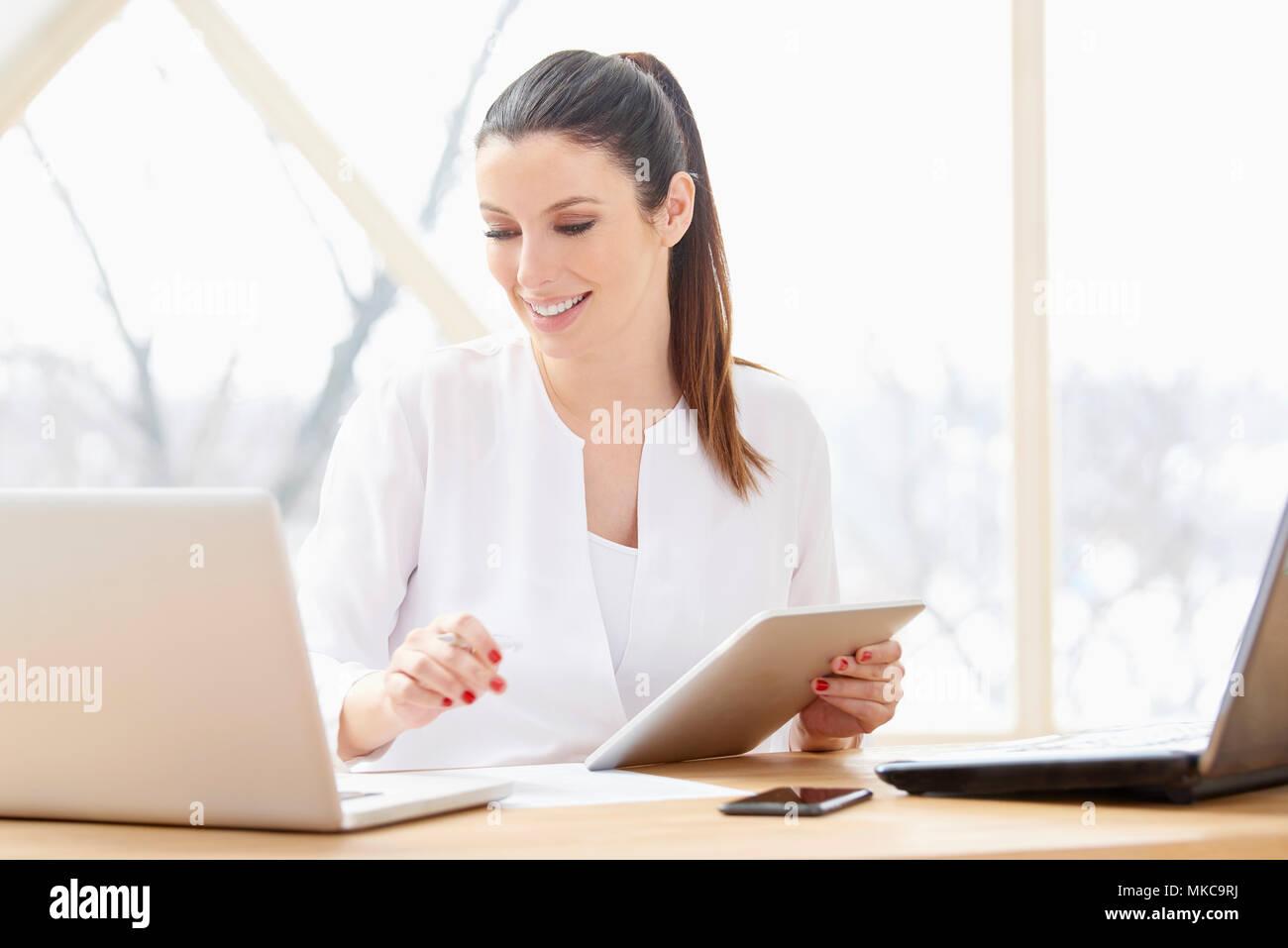 Ritratto di attraente giovane imprenditrice utilizzando tavoletta digitale e computer in ufficio. Immagini Stock