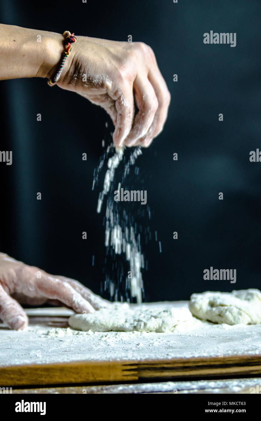 Impasto ormeggiata sulla tavola di legno, tradizionale pretzel preparazione, baker rendendo la pasta di pane nel forno. mani giocate con farina e pasta. Immagini Stock