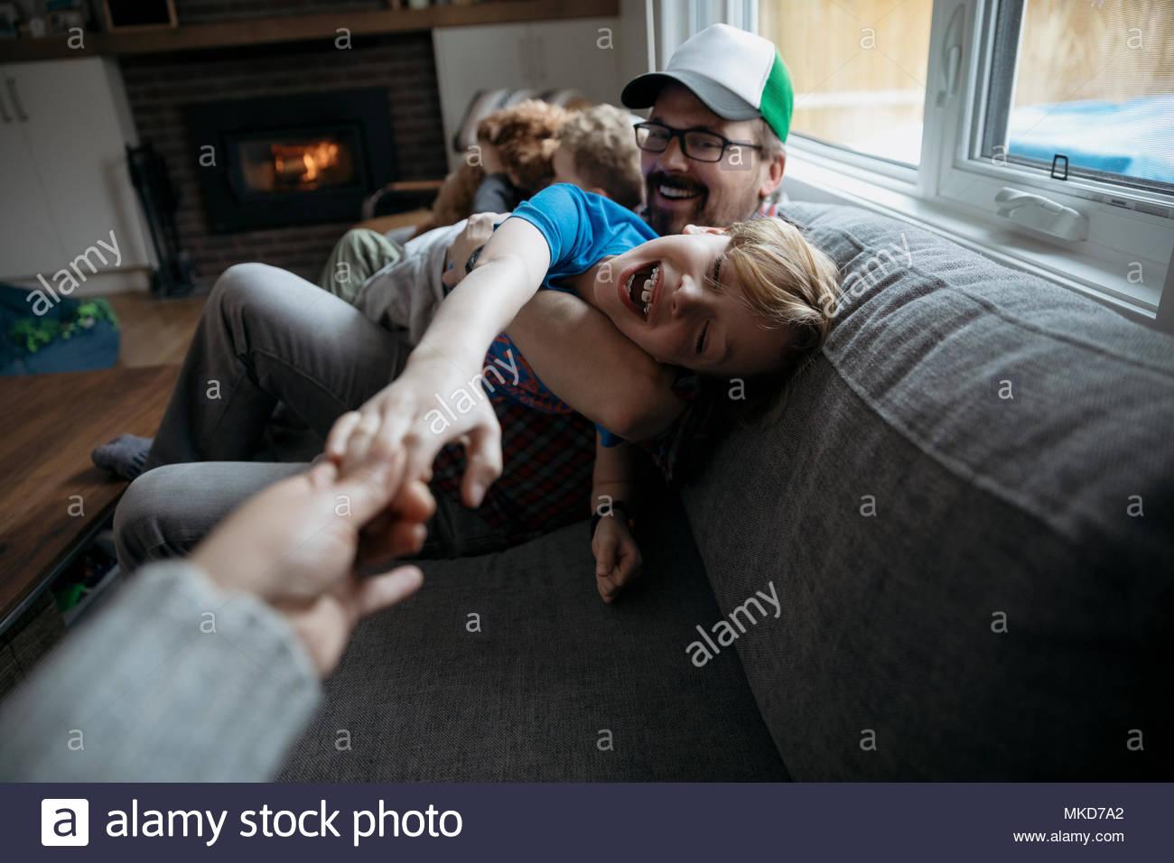 Punto di vista personale famiglia giocando sul divano Immagini Stock