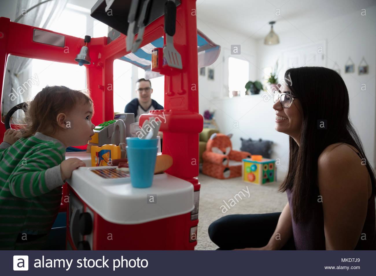I genitori guardare baby figlio giocando in cucina giocattolo Immagini Stock