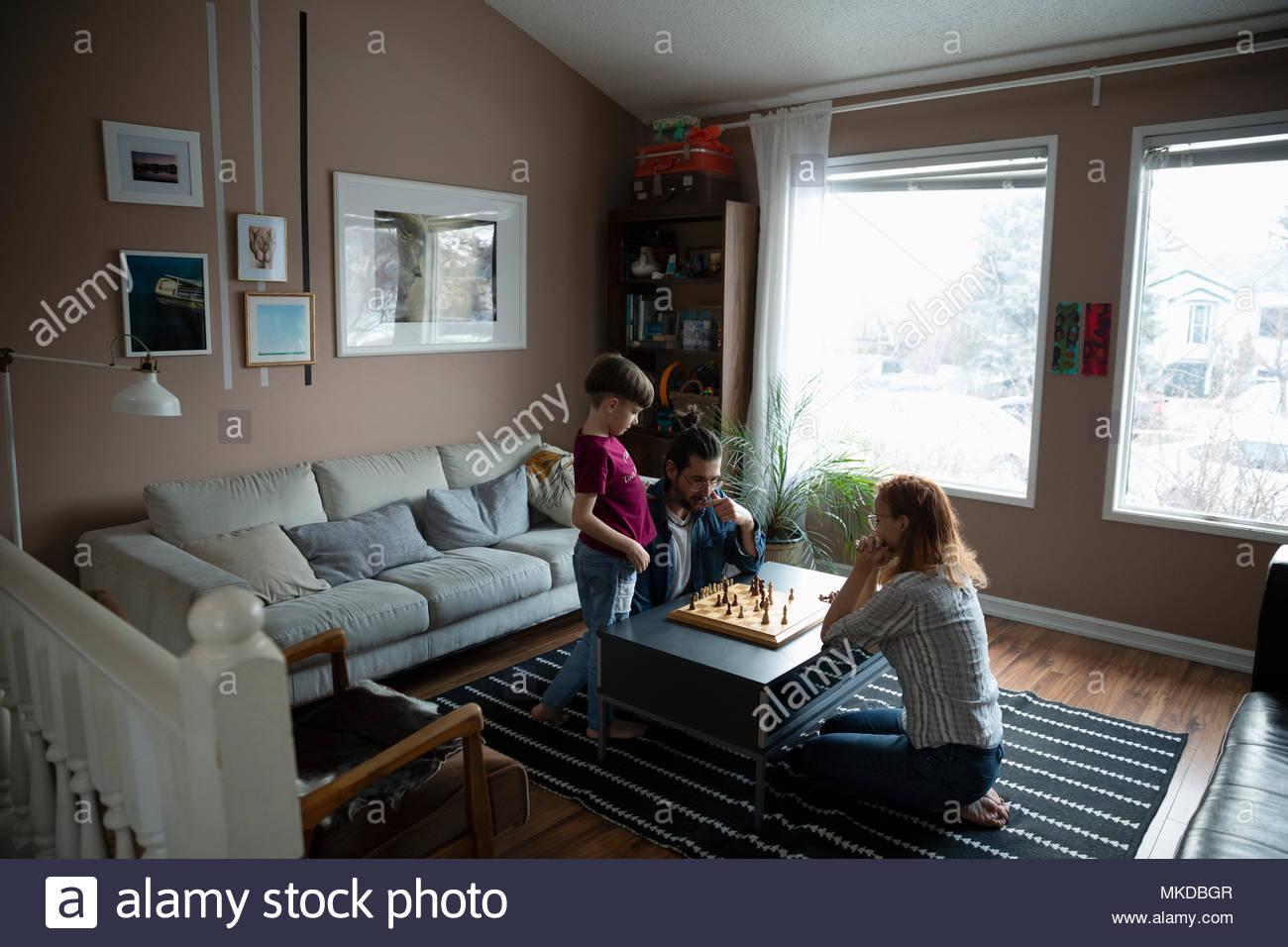 Famiglia giocare a scacchi al soggiorno tavolo da caffè Foto ...