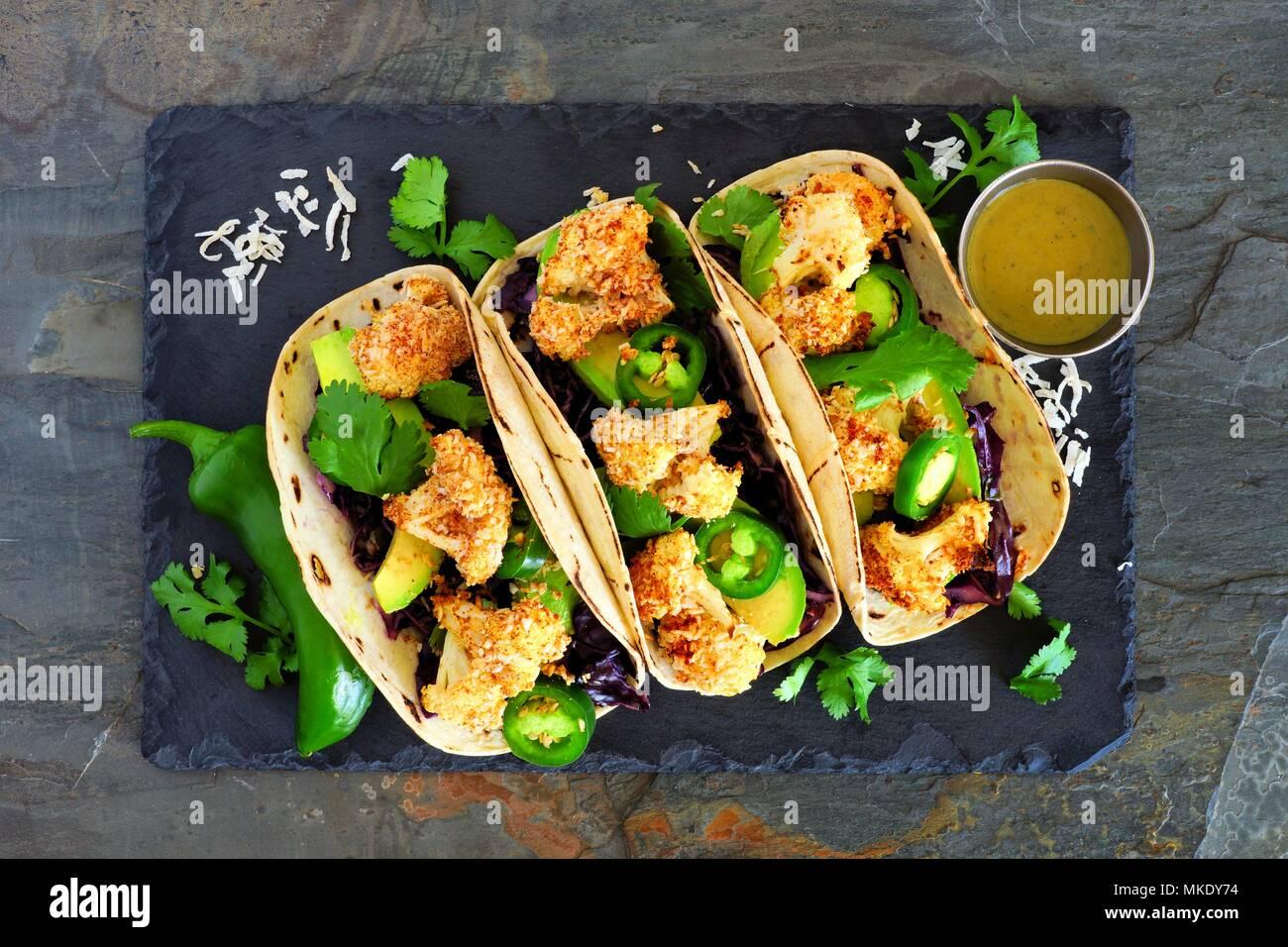 Arrosto di cavolfiore noce di cocco tacos. Sana, pasto vegano. Al di sopra di visualizzare su un ardesia scura sullo sfondo di pietra. Immagini Stock