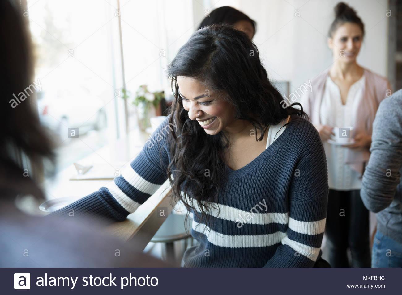 Ridendo giovane donna parlando con un amico in cafe Immagini Stock
