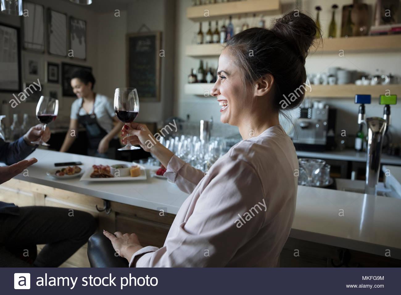 Ridendo, spensierata giovane donna di bere il vino rosso in bar Immagini Stock