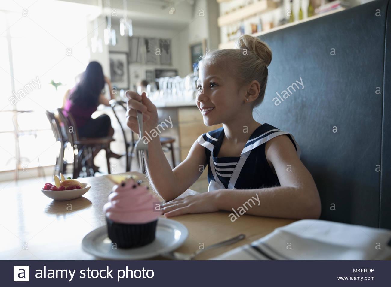 Happy girl festeggia il compleanno, mangiare cupcake in cafe Immagini Stock