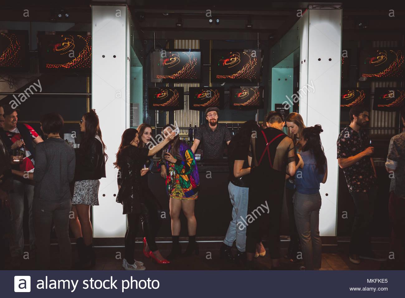 Milennials appendere fuori, tenendo selfie in bar Immagini Stock