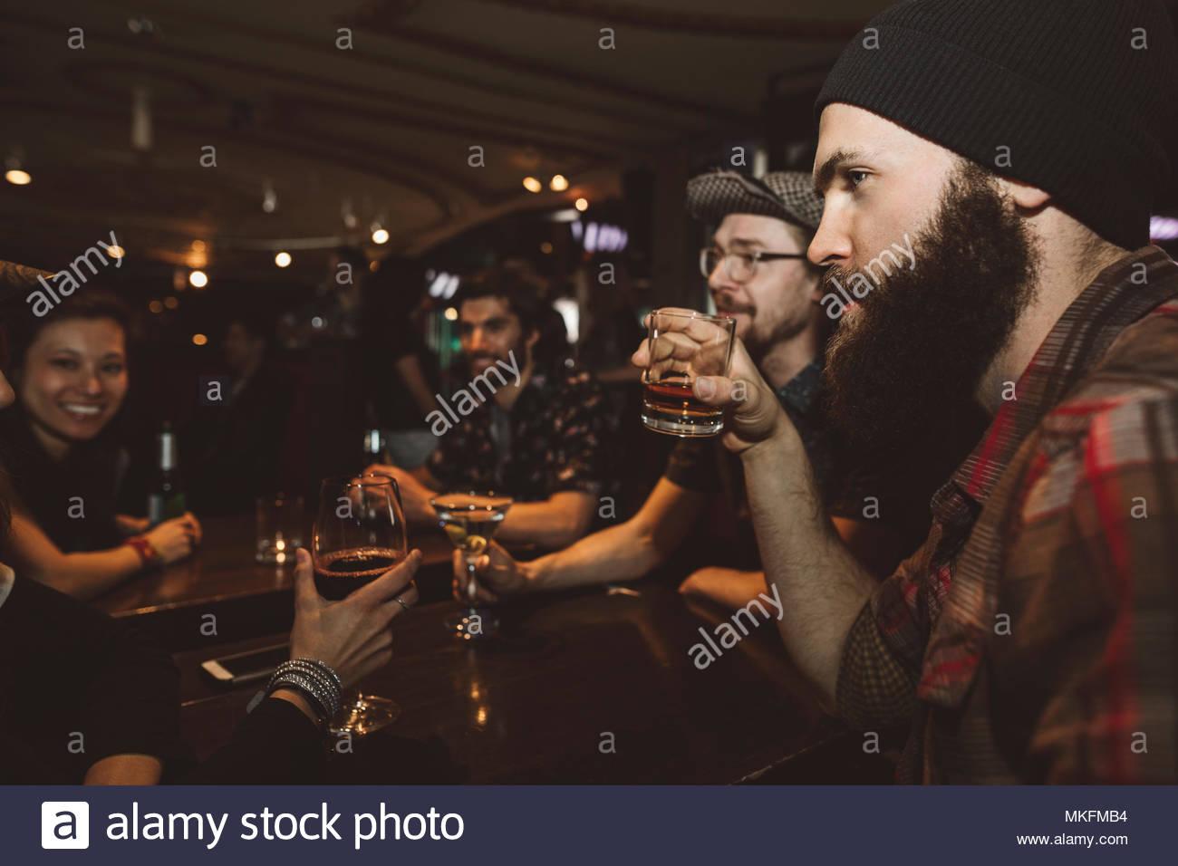 Maschio tanga millenario di bere whisky in bar, ascolto di amici Immagini Stock