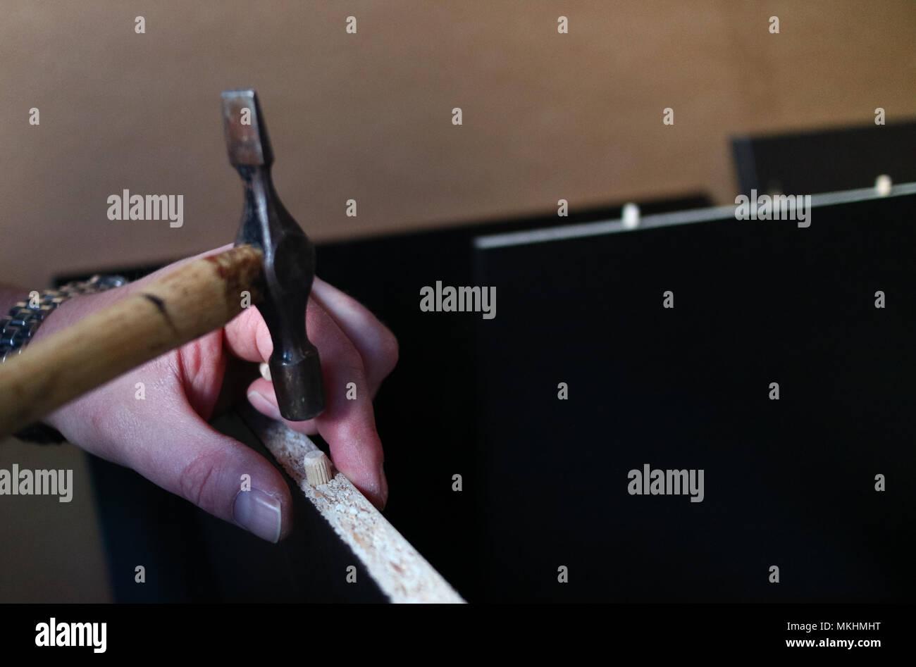 Un primo piano di un uomo con le mani in mano utilizzando un martello per costruire flat-pack mobili Foto Stock