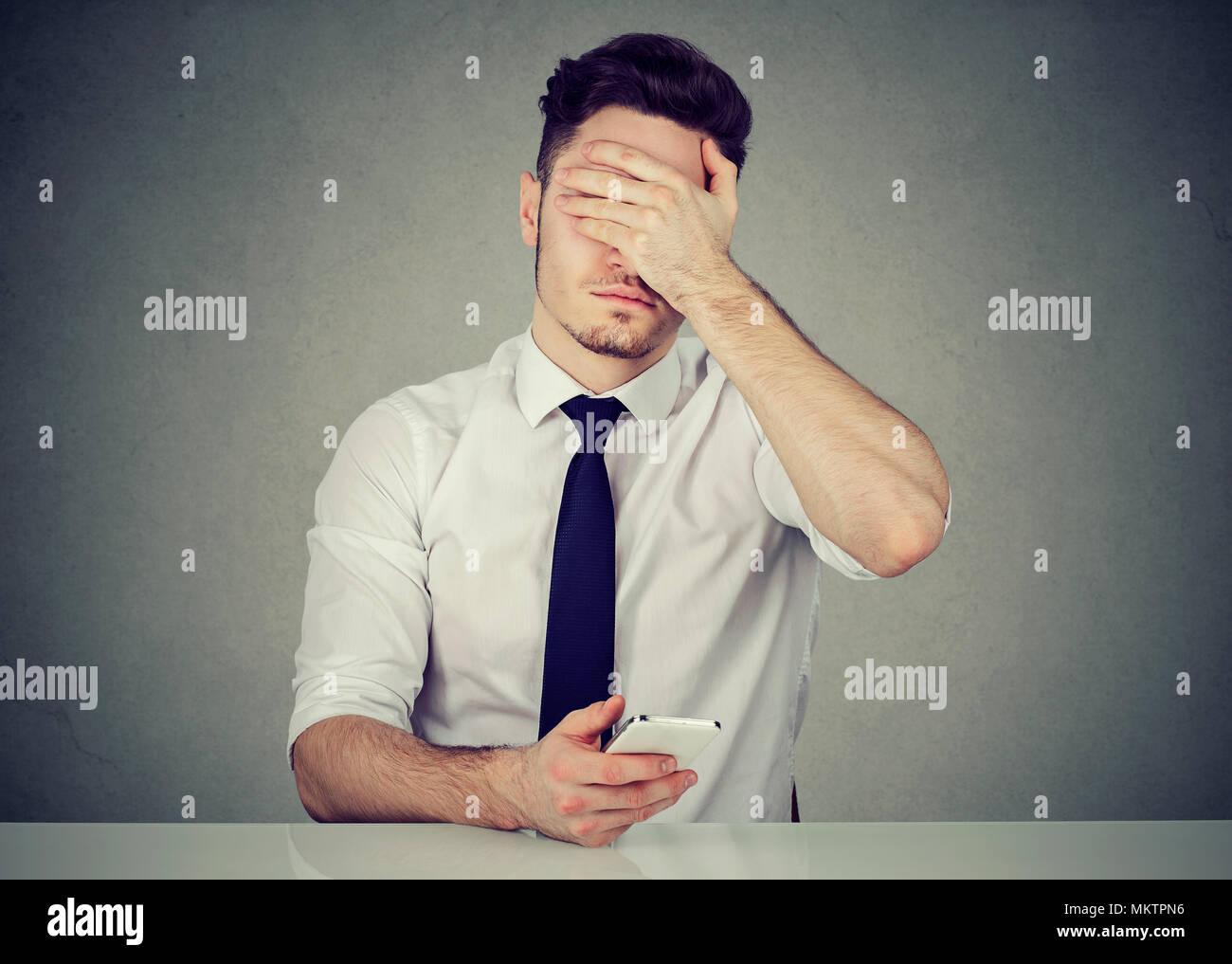 Giovane uomo formale tramite telefono e che ricopre la faccia a causa di questo errore mentre si lavora Immagini Stock