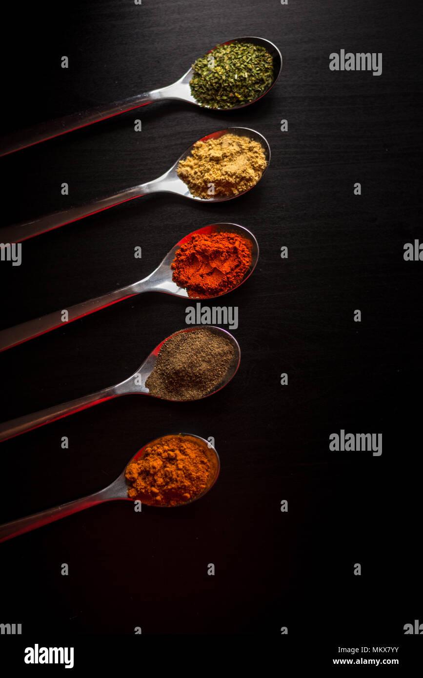 Spezie colorate in argento cucchiai, collocato su un tavoli in legno nero. Peperoncino, pepe, sale, basilico, senape Immagini Stock