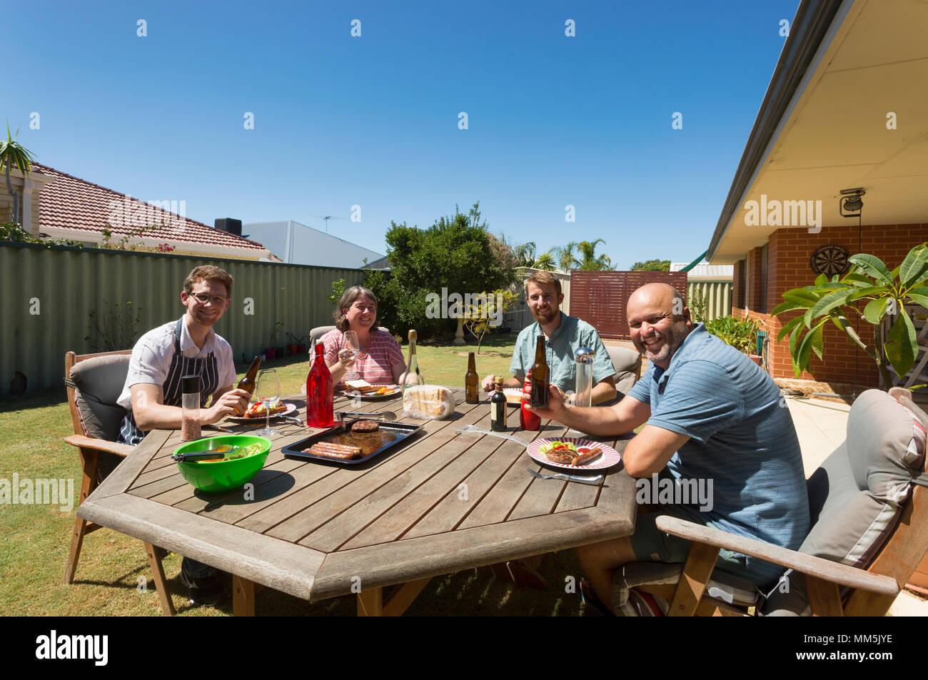Un gruppo di persone mangiare all'aperto con barbecue cibo. Immagini Stock