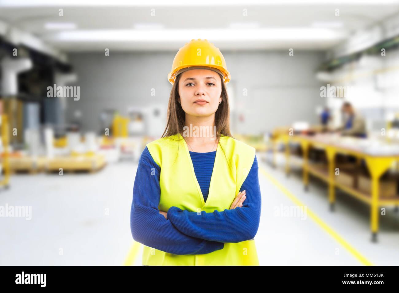 Orgoglioso fiducioso giovane donna ingegnere con le braccia incrociate come supervisore professionale concetto sulla coperta di sfondo in fabbrica Immagini Stock