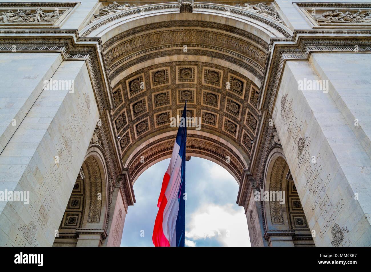 Tri-Color bandiera francese volare al di sotto di Arc de Triomphe, Parigi, Francia Immagini Stock