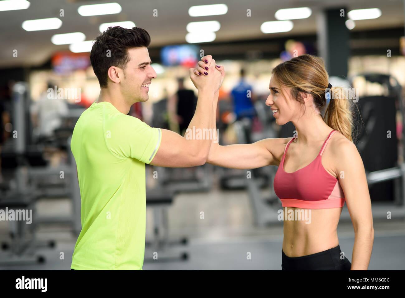 69634d604692 Sorridente giovane uomo e donna facendo alta cinque in palestra. Paio di  indossare abbigliamento sportivo