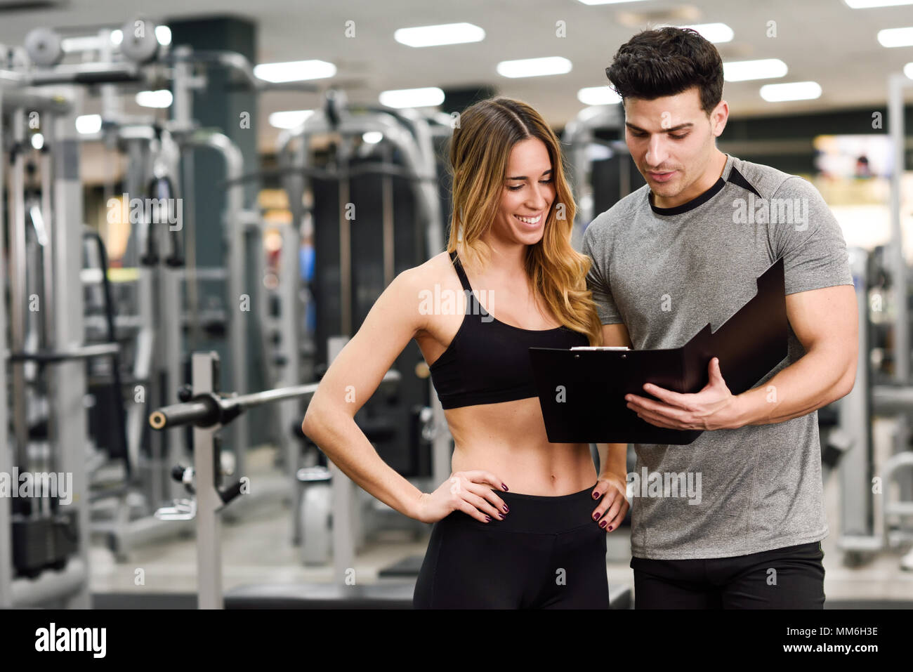 b216fc53aed8 Personal trainer e cliente guardando i suoi progressi in palestra. Athletic  l uomo e la donna che indossa abbigliamento sportivo.