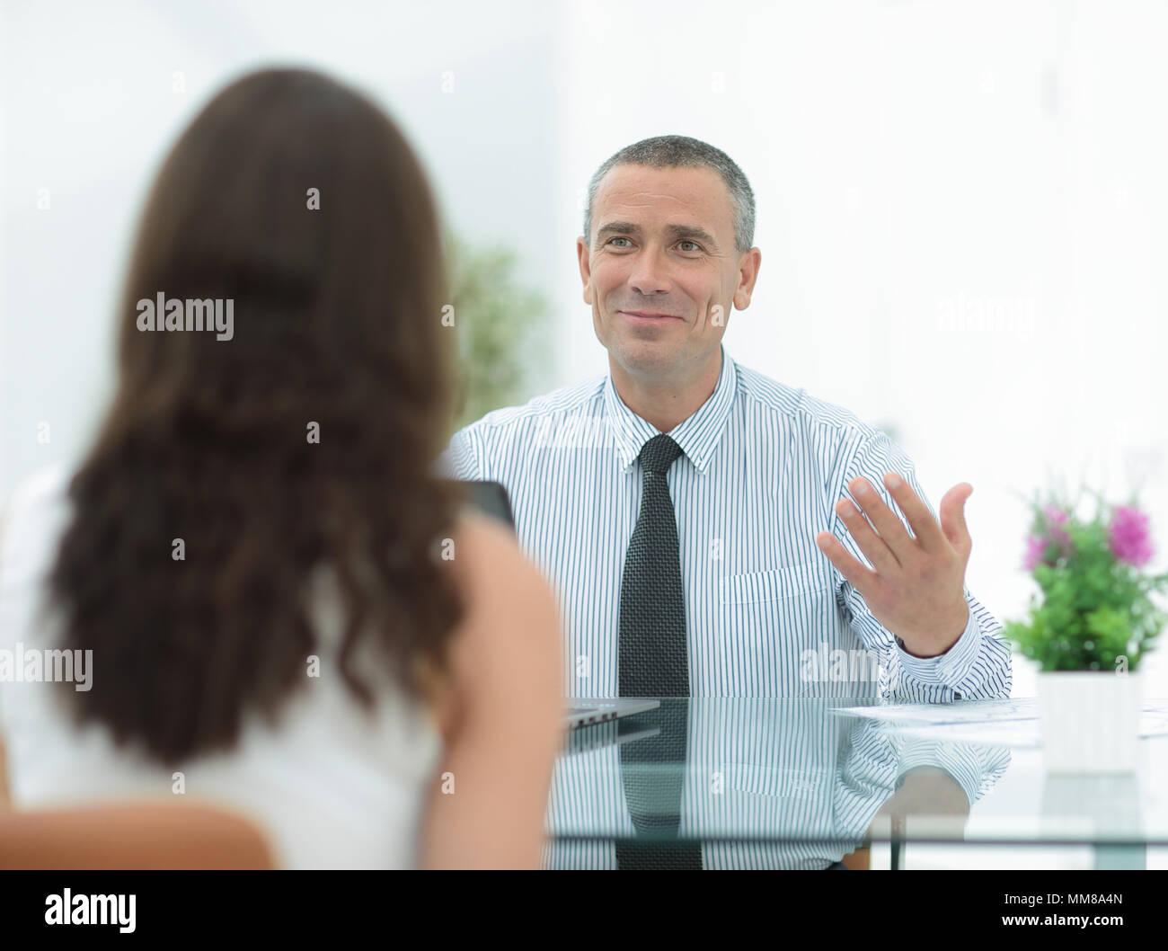 Il consulente aziendale si siede alla sua scrivania e di consultarsi con i loro client Immagini Stock