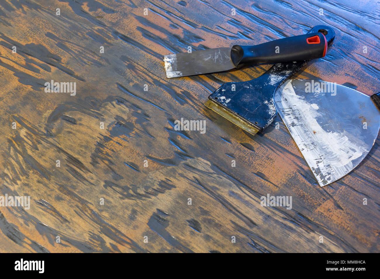 Dipingere i raschiatori e i coltelli puddy su legno foto