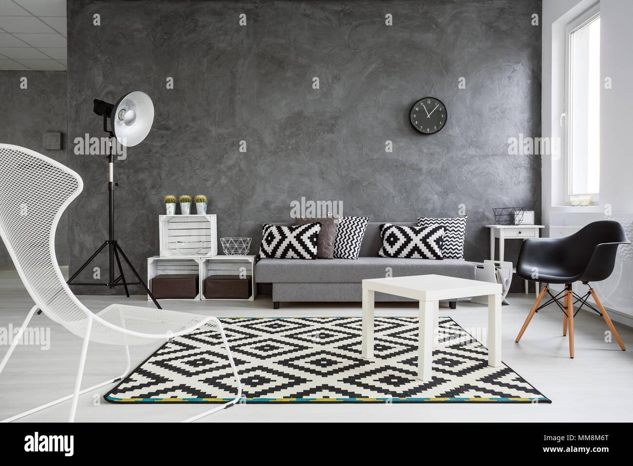 Spazioso soggiorno arredato con stile pareti grigio bianco con pavimento in legno e il bianco for Soggiorno arredato