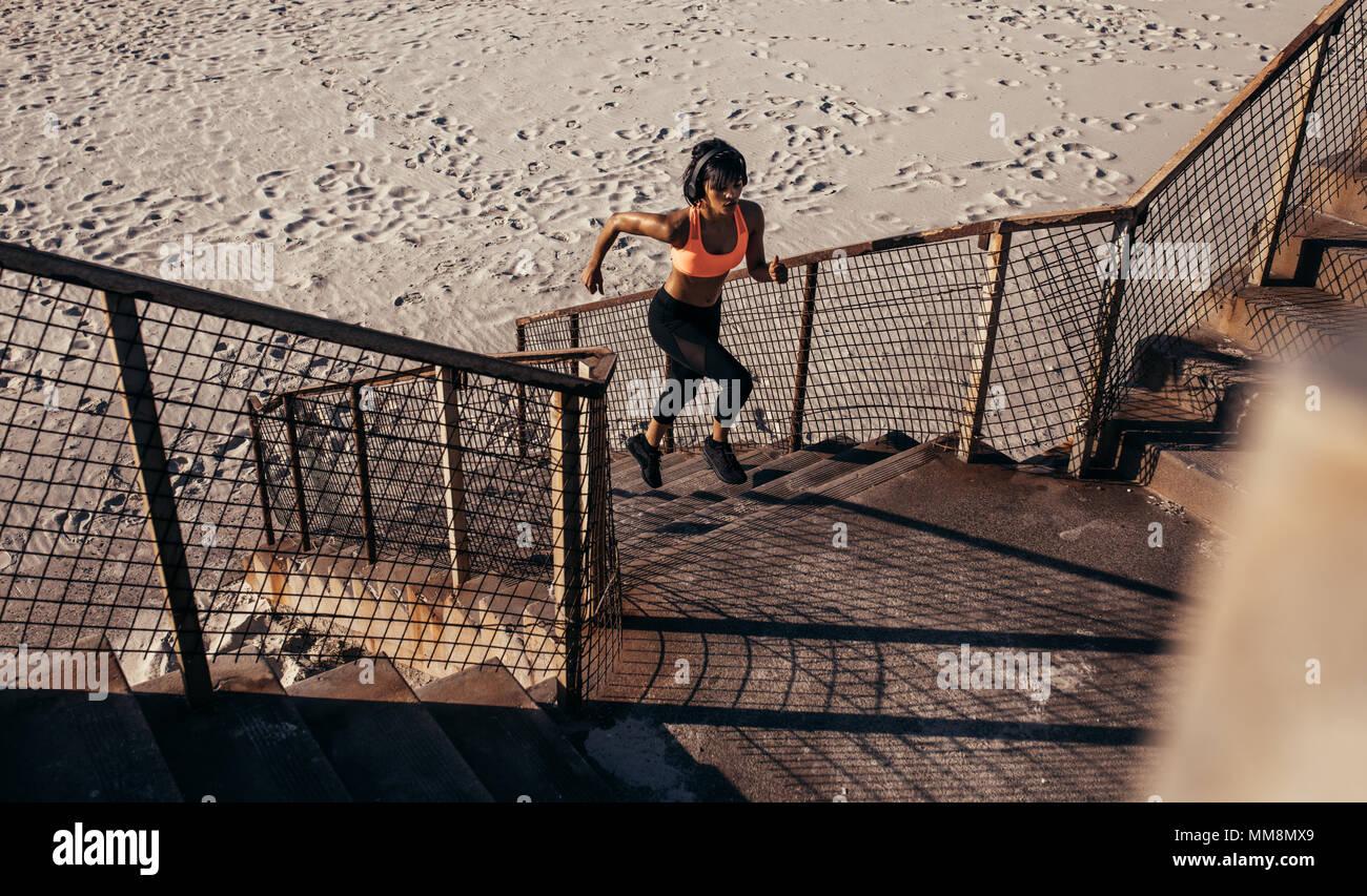 Athletic donna corre su per i gradini sulla spiaggia. Atleta in sportswear formazione sui passi concreti. Immagini Stock