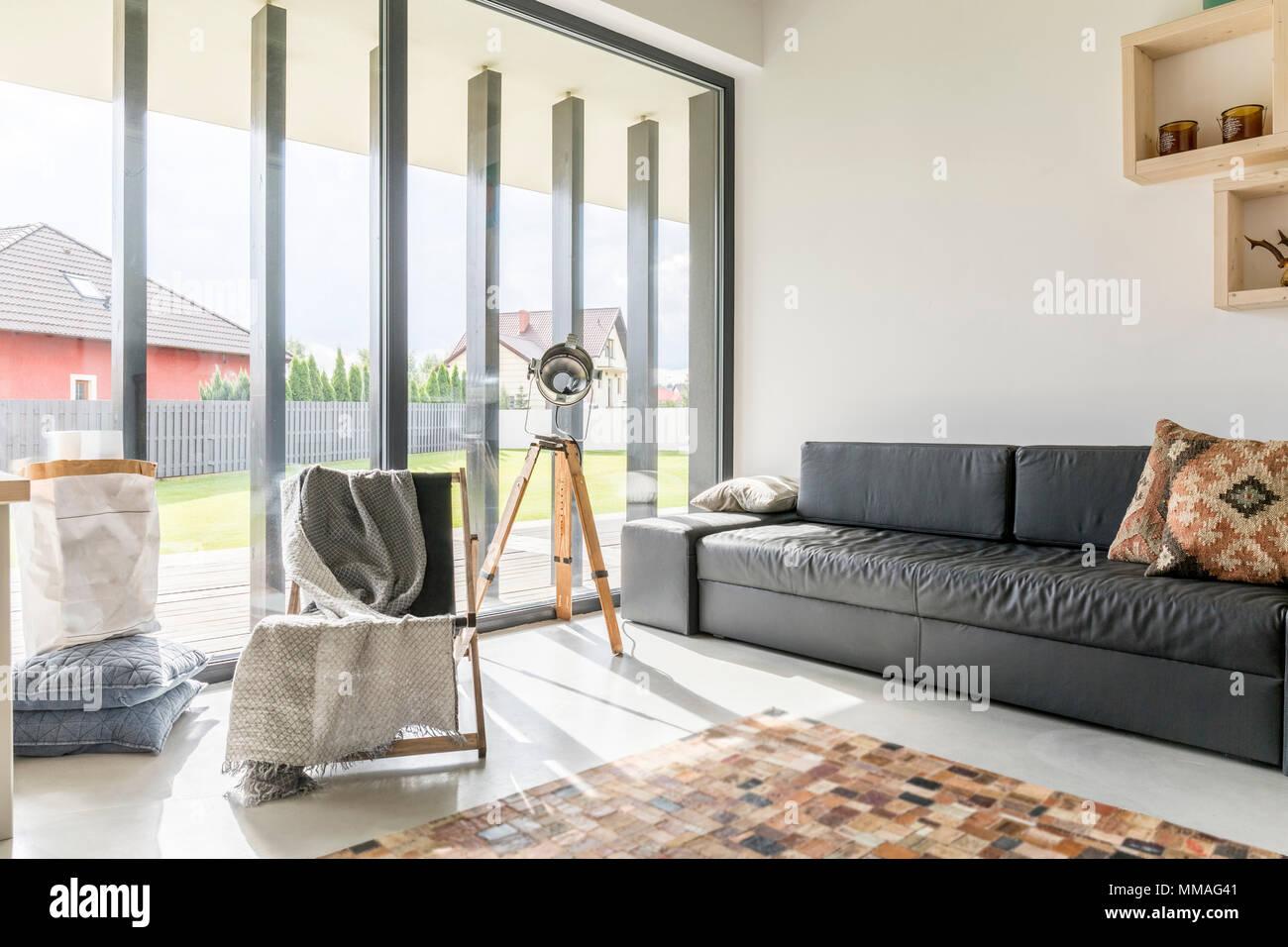 Soggiorno con finestra a parete nera divano e la moquette foto