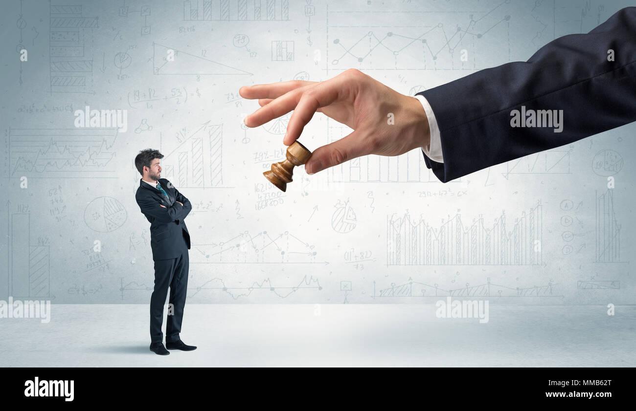 Piccolo imprenditore è paura di fare il passo successivo nella sua partita a scacchi con grafici, Grafici e report sullo sfondo Immagini Stock