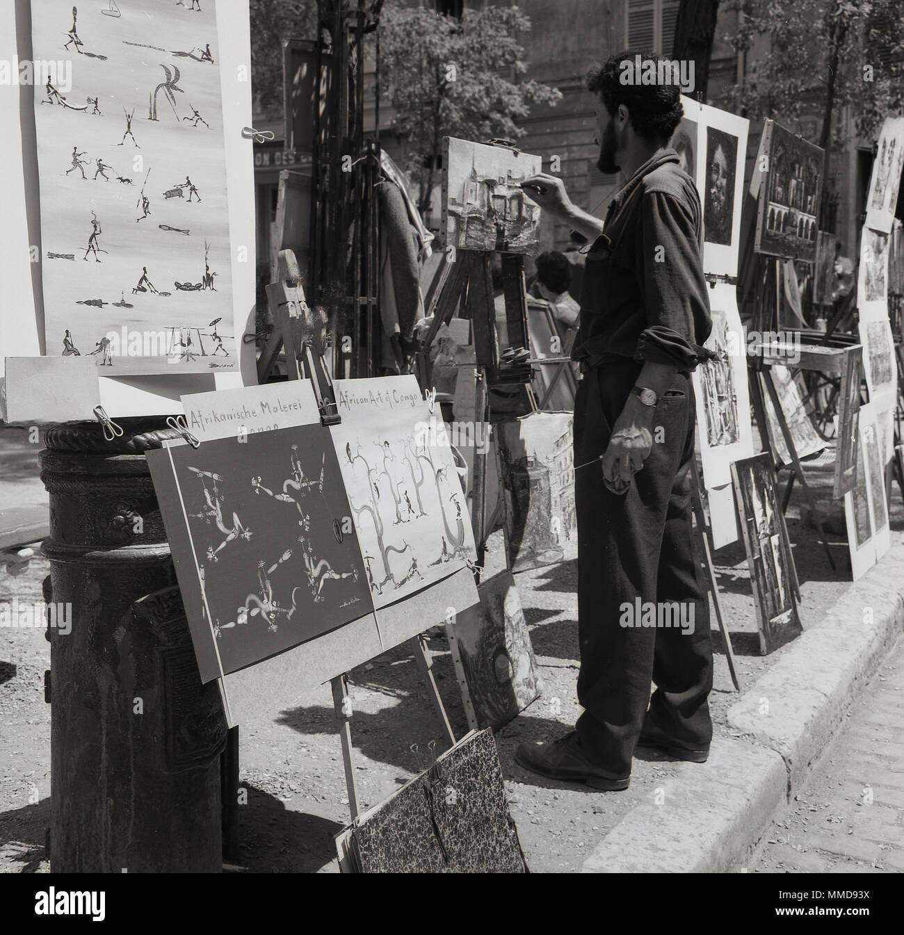 Degli anni Cinquanta, foto storiche di un maschio di artista di strada in una pittura su tela a La Place du Tertre a Montmartre, Paris, Francia, una zona famosa per i suoi artisti e storia artistica, Immagini Stock