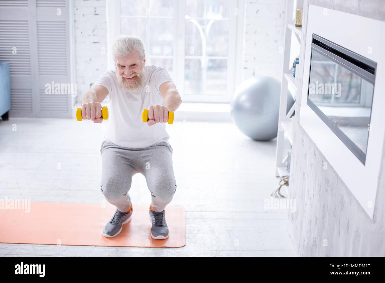 Bel uomo anziano holding manubri e facendo squat Immagini Stock