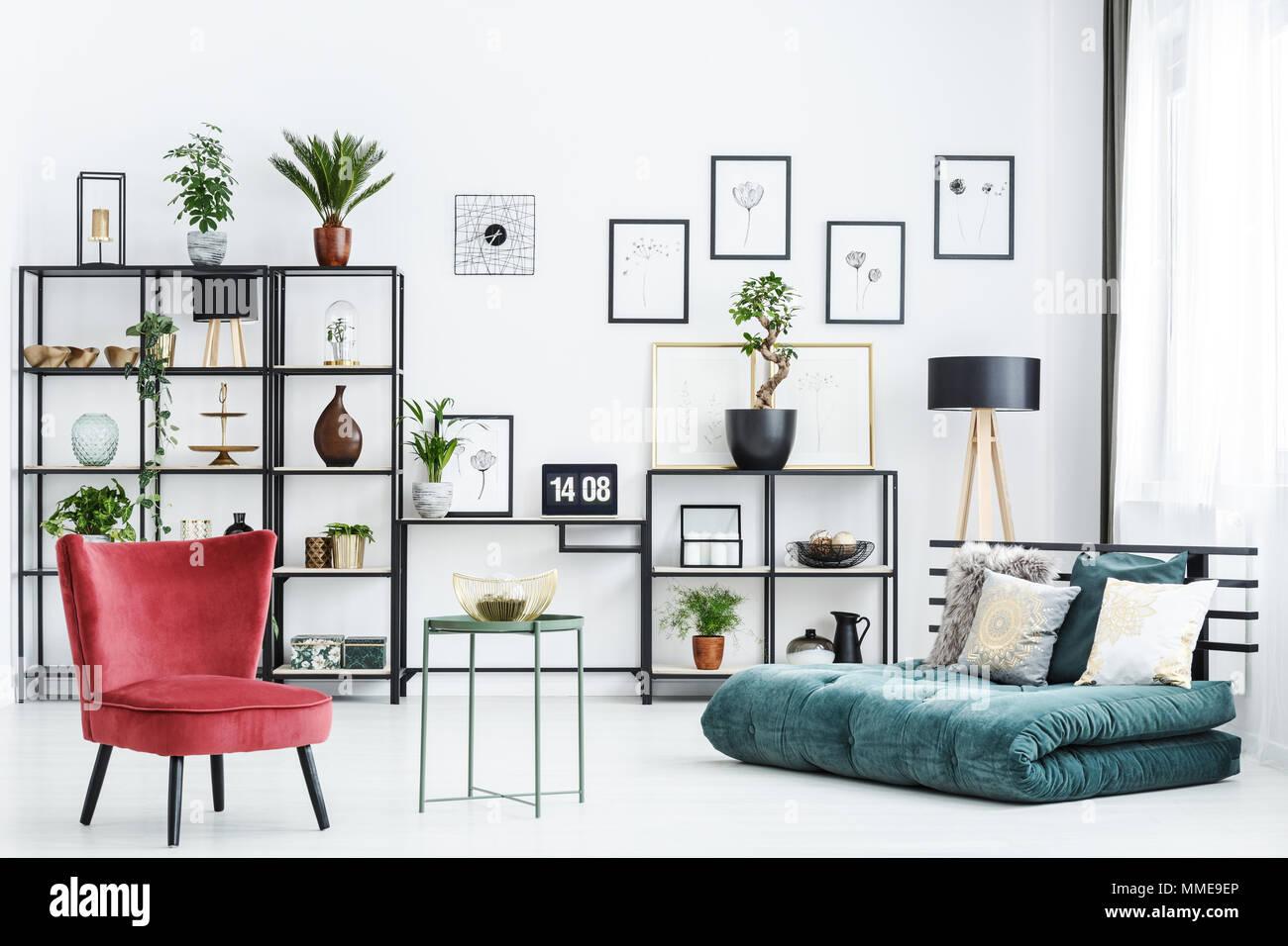 Tabella tra la sedia rossa e verde futon in casa ufficio interno con poster e piante Immagini Stock