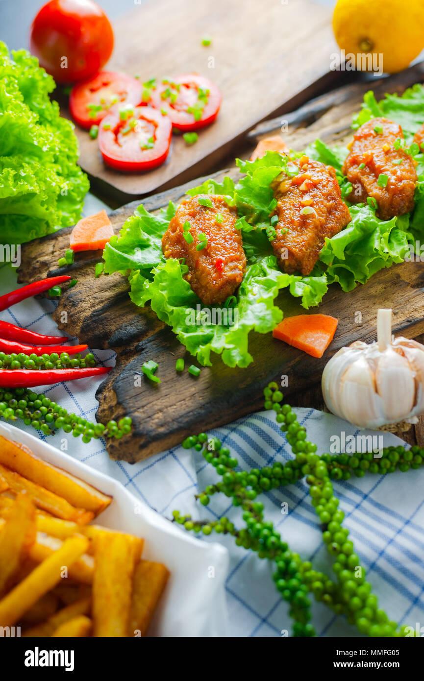 Alette di pollo fritte con peperoncino piccante salsa rustico che serve bordo, erbe e verdure su sfondo di legno. Immagini Stock