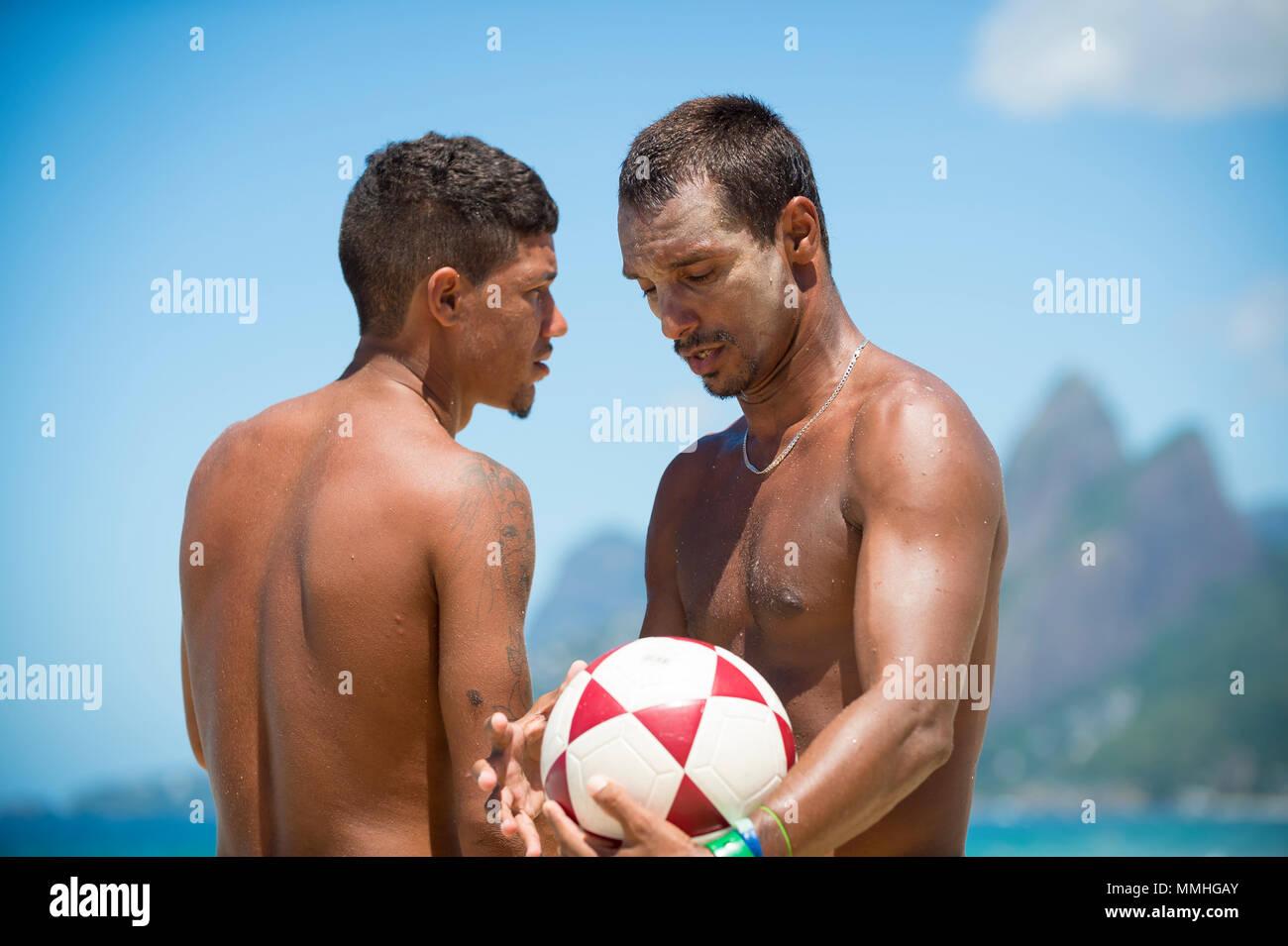 RIO DE JANEIRO - Febbraio 9, 2017: giovane brasiliano uomini stare sulla spiaggia con un calcio al Arpoador, contro una vista dello skyline di due fratelli mountain Immagini Stock