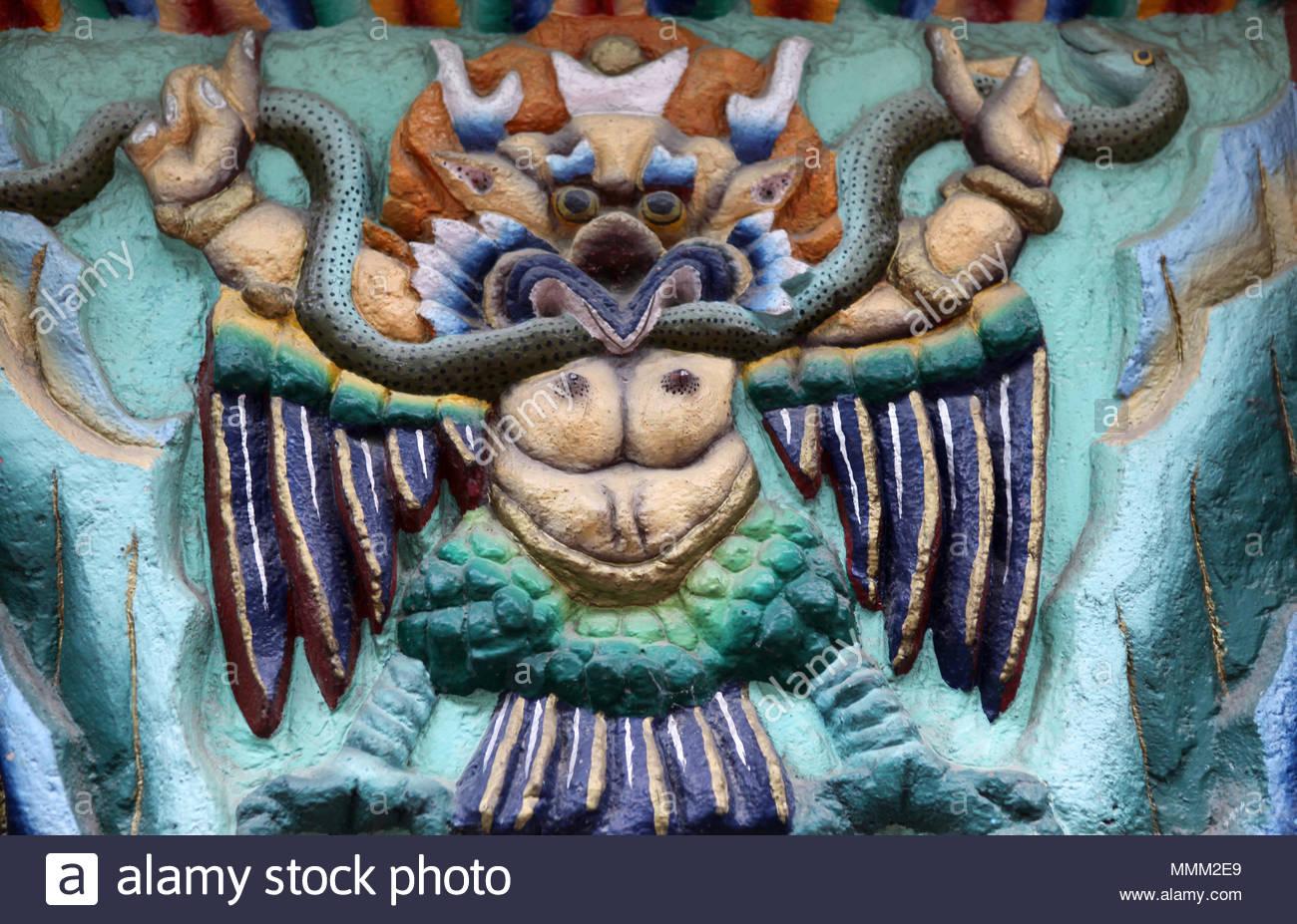 """Dettaglio del rilievo raffigurante arte mitico uccello-come creatura afferrare un serpente nella sua talons """" su un edificio di Gangtok, Sikkim. Immagini Stock"""