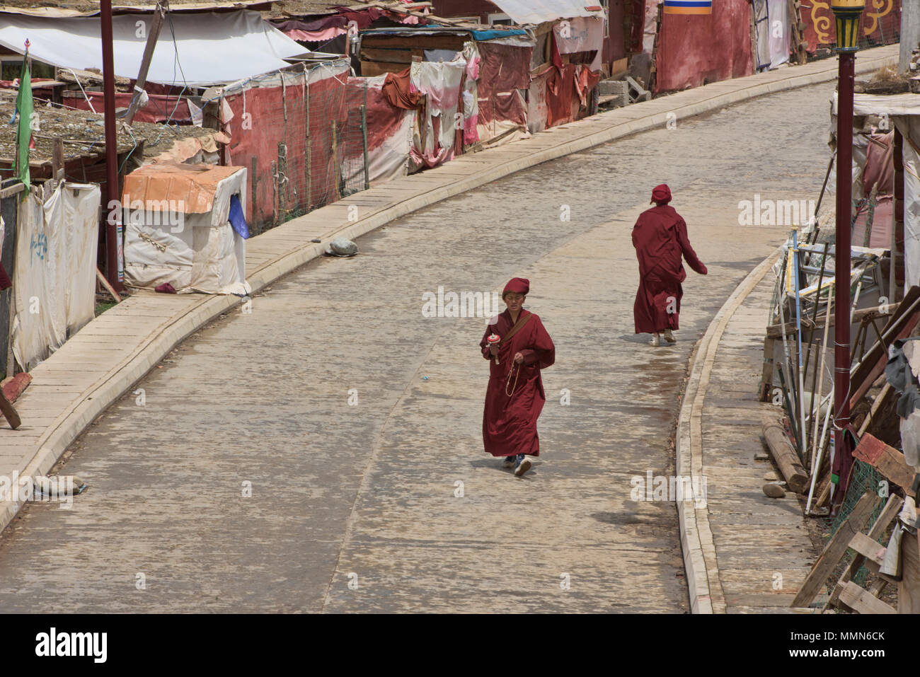 Il Tibetano monache la filatura ruote della preghiera, Yarchen Gar, Sichuan, in Cina Immagini Stock