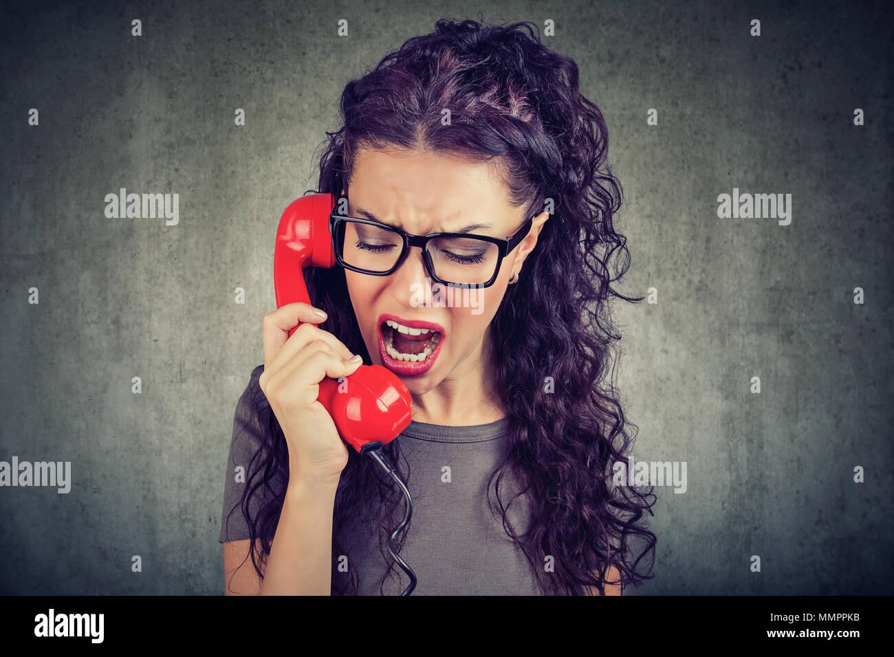 Giovani arrabbiati donna urlare al telefono Immagini Stock