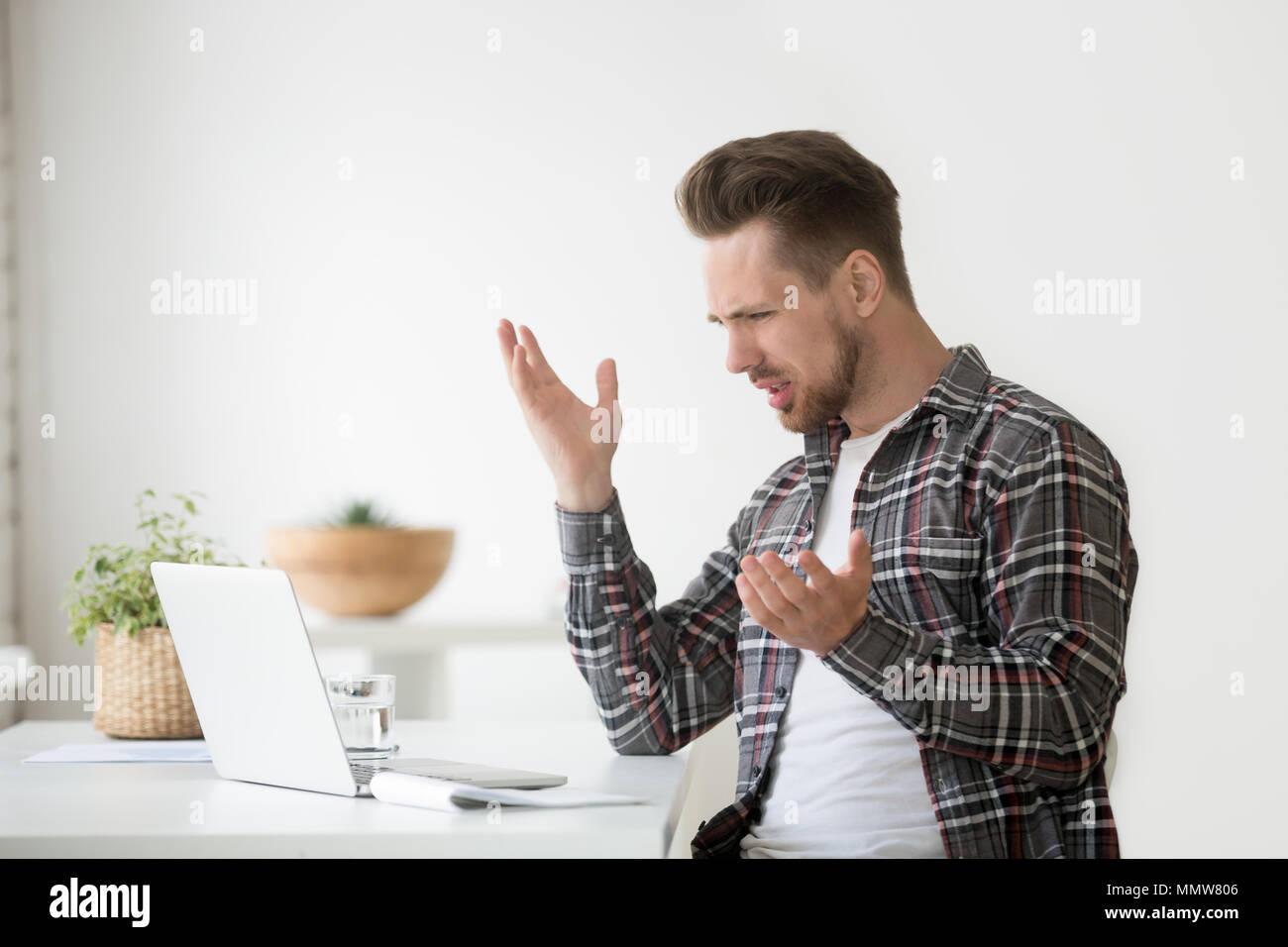 Confuso angry man frustrati dal problema online, odio lapt bloccato Immagini Stock