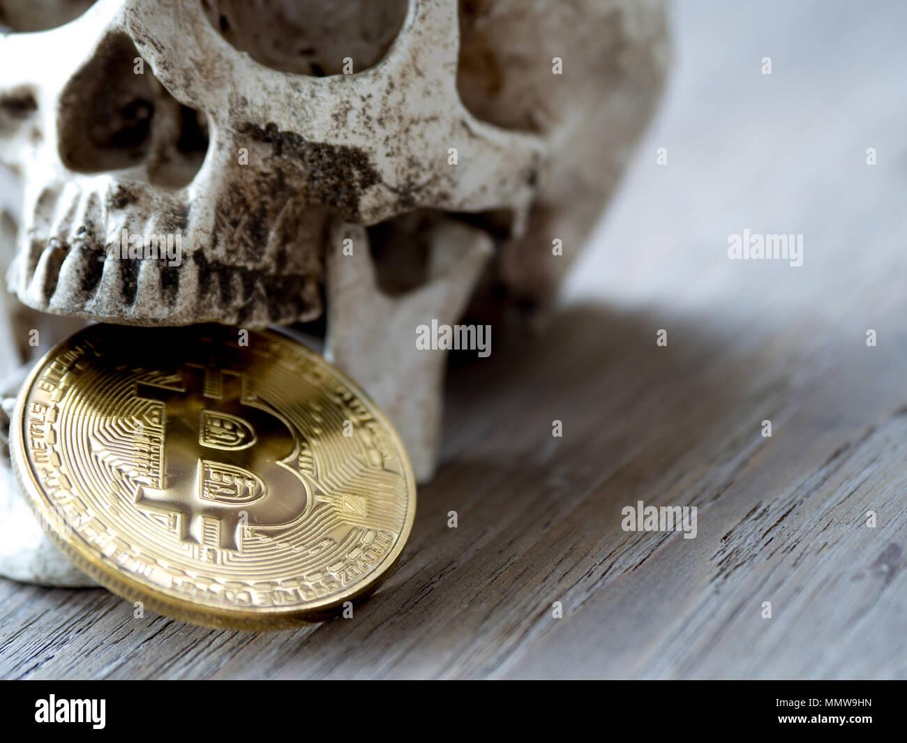 Close up del cranio di mordere Golden bitcoin sul tavolo di legno. Il concetto di investimento e di fluttuazione di bitcoin e cryptocurrency. La sensazione di disap Immagini Stock