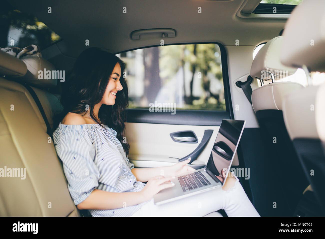 Bella donna d'affari sta usando un computer portatile mentre è seduto sul sedile posteriore in auto Foto Stock