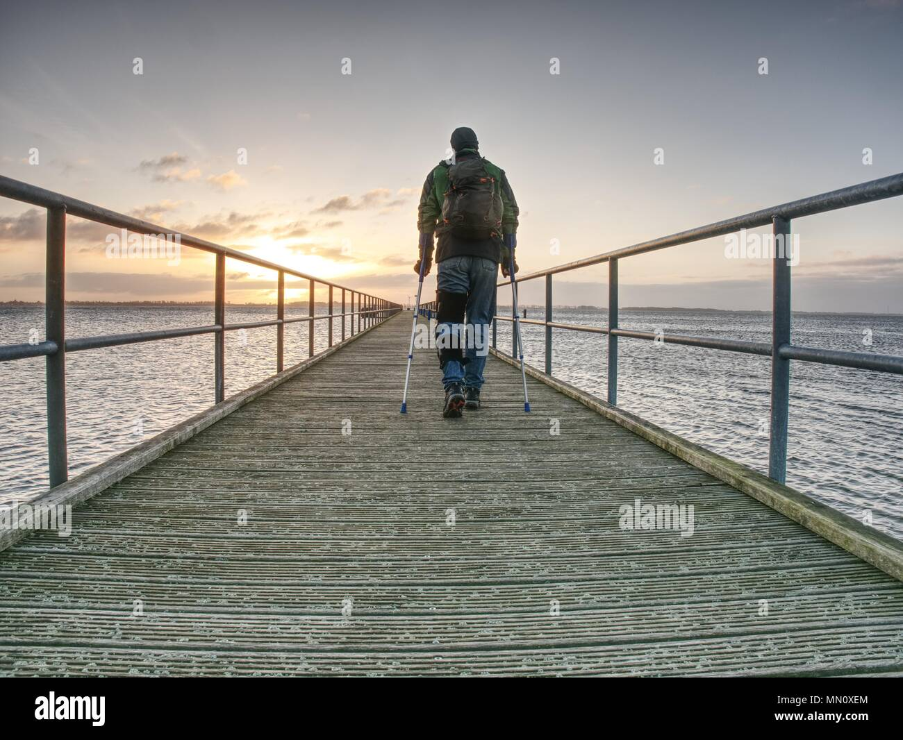 Ferire l'uomo con giacca con cappuccio e avambraccio stampelle cercando tristemente in acqua di mare. Supporto di viaggiatori sul ponte del mare entro la mattina e pensare. Nostalgico Immagini Stock
