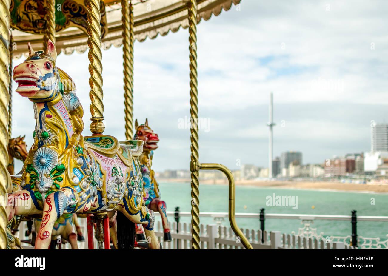 Una vista dal Molo di Brighton con la tradizionale Giostra cavalli sul molo e la British Airways i360 torre di osservazione a distanza. Immagini Stock