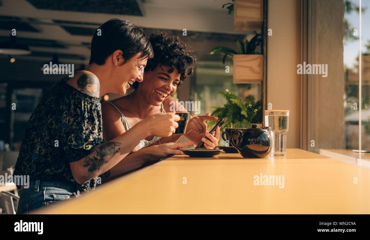 Due donne che utilizzano il telefono cellulare e di bere il caffè al caffè femmine spendere il loro tempo libero presso la caffetteria. Immagini Stock