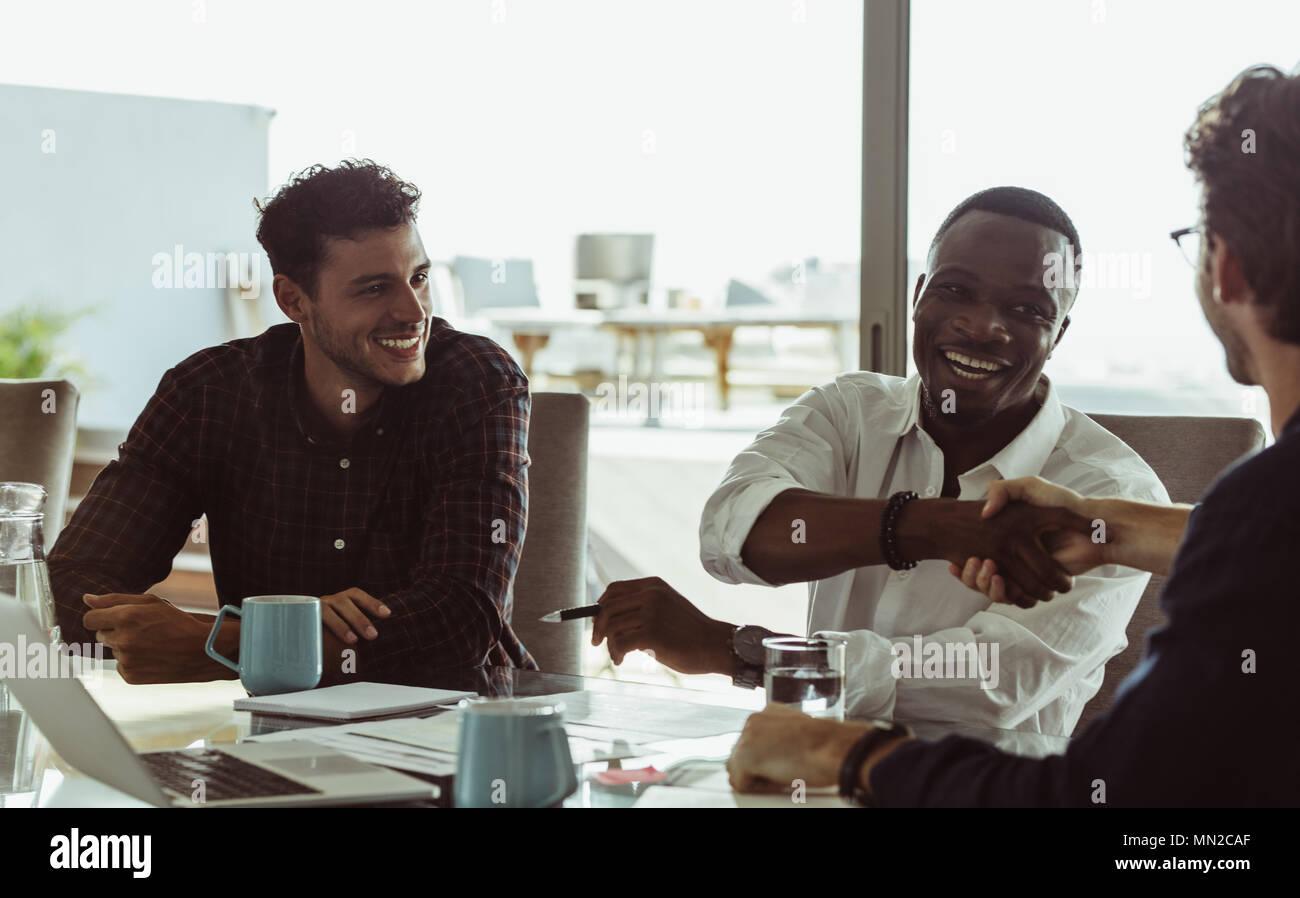 Discutere gli imprenditori lavorano seduti ad un tavolo per conferenza in ufficio. Gli uomini si stringono la mano e sorridente durante una riunione di affari. Immagini Stock