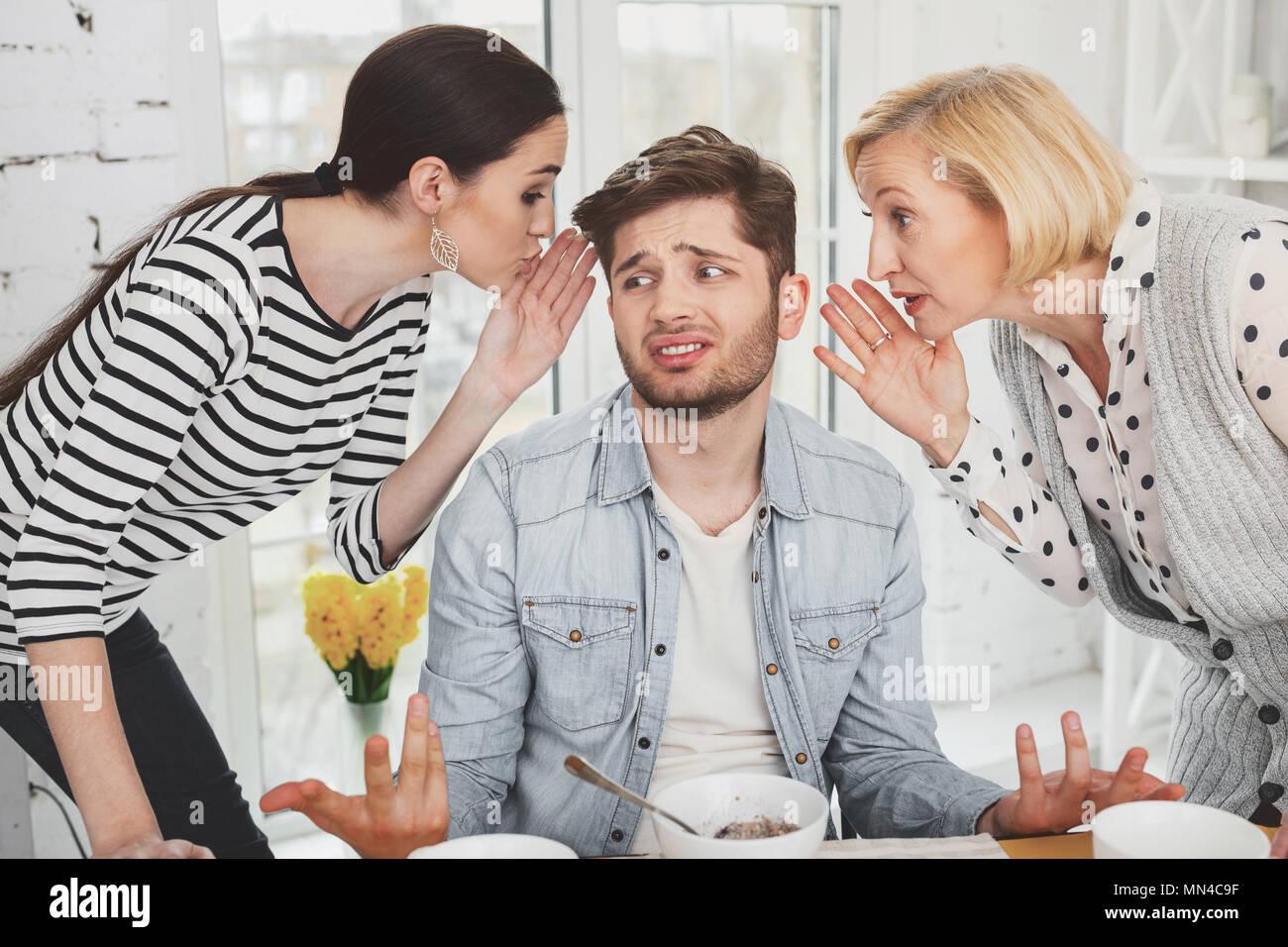 Cupa giovane uomo che ascolta le donne Foto Stock