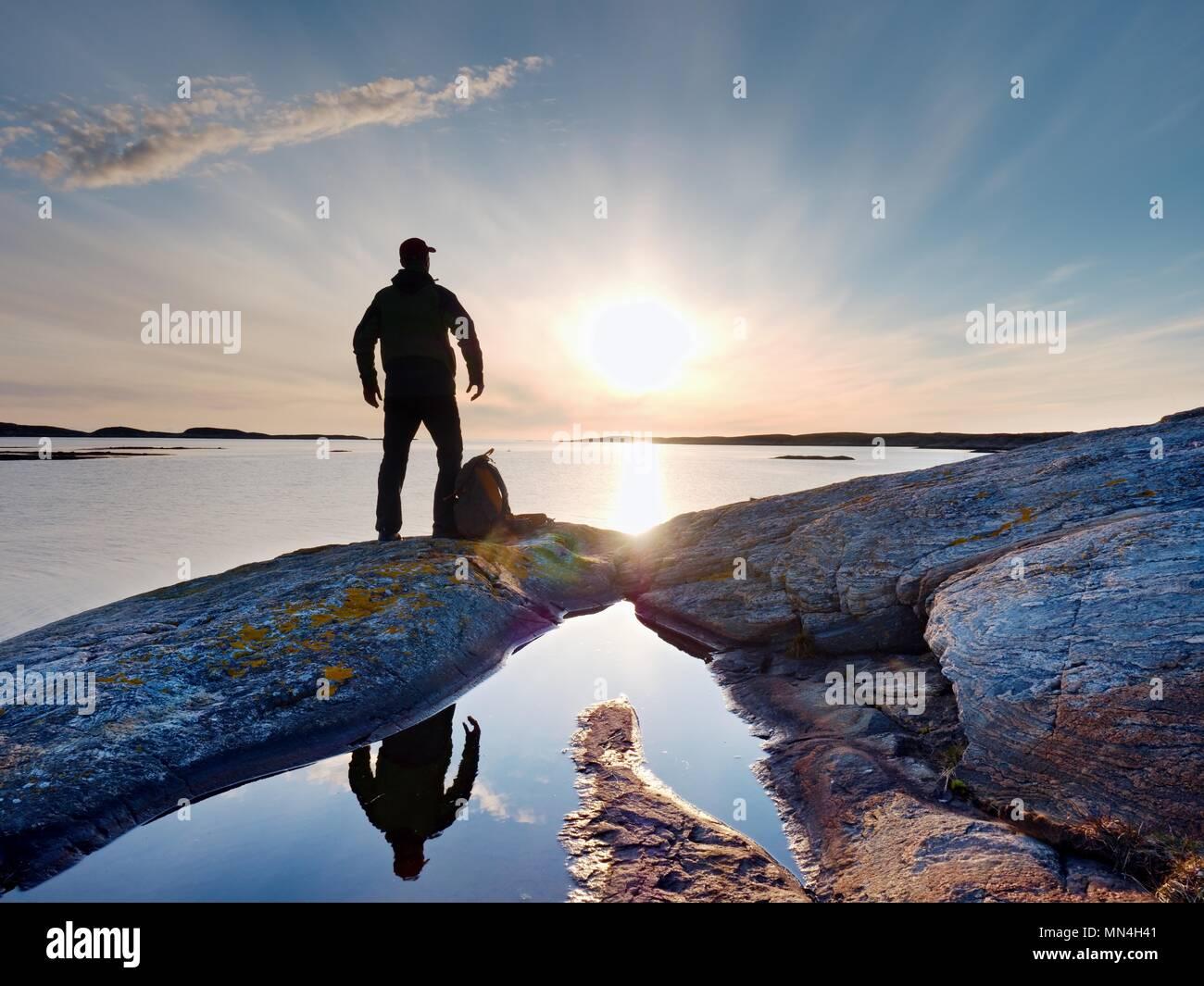 Silhouette di un solo uomo che guarda verso la vibrante del tramonto. Flare e riflessi in acque poco profonde del livello del mare Immagini Stock