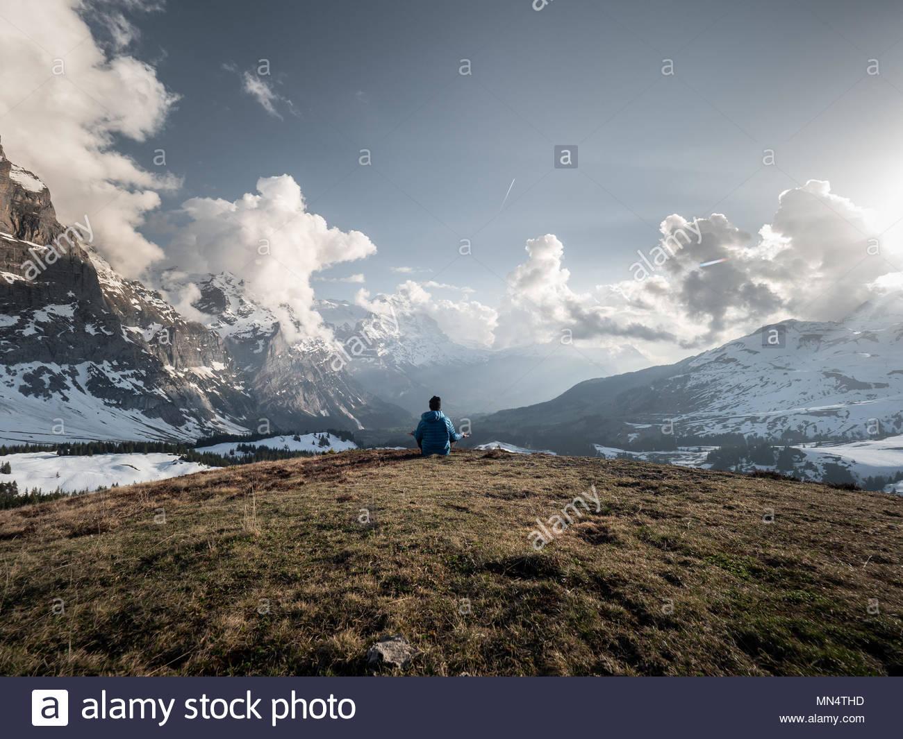 Unico uomo seduto sulla collina che si affaccia sulla catena montuosa circostante e meditando, idilliaco panorama alpino Immagini Stock
