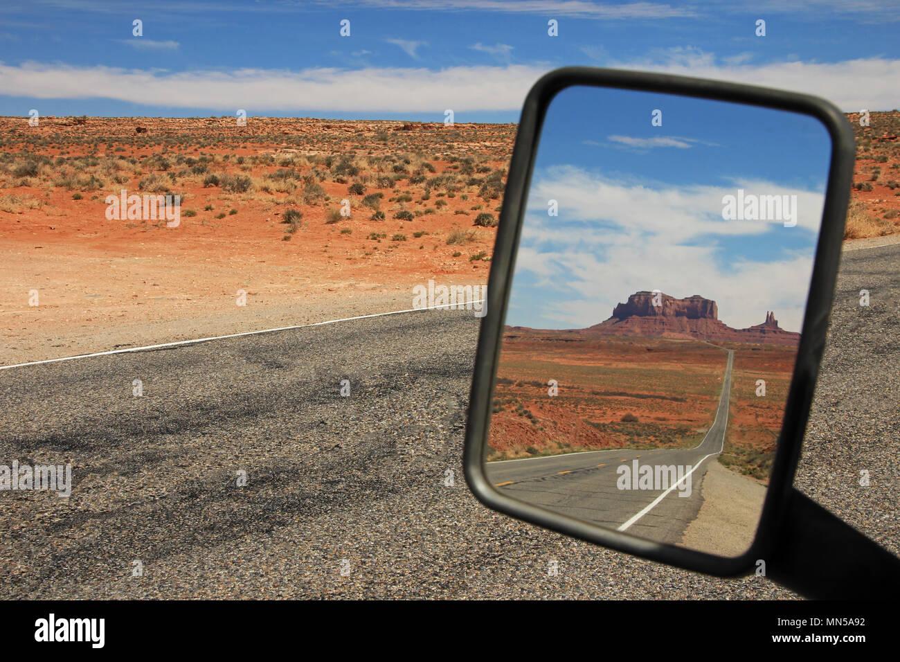 Specchietto retrovisore vista della strada che corre attraverso la Monument Valley, Utah Immagini Stock
