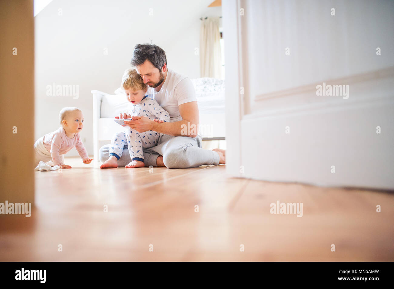 Padre e figli dei bimbi con lo smartphone seduta sul pavimento a casa prima di andare a dormire. Congedo di paternità. Immagini Stock